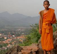 High life: A monk (top) stands atop Phu Si, a sacred temple that overlooks Luang Prabang, one of the most enticing destinations in Asia and a sacred site of Theravada Buddhism. Luang Prabang is now a World Heritage site due to its numerous temples, rich culture, lovely colonial architecture and captivating location at the confluence of the Mekong and Nam Khan rivers. An interior view (below) from Pak Ou cave overlooking the Mekong River less than two hours from Luang Prabang, where hundreds of Buddhas are stored. | JEFF KINGSTON PHOTOS