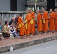 Open alms: Luang Prabang monks beg for breakfast, so bestowing merit on donors.