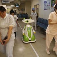 Future shock: Staff, including a receptionist robot, work at a hospital in Aizu Wakamatsu, Fukushima Prefecture. | AP PHOTO