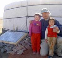Chilling out: Yasuyuki Fujimura poses beside one of his non-electric fridges with two young children who live on the vast Mongolian grasslands, and whose lives could be greatly improved thanks to his inventiveness. | YASUYUKI FUJIMURA PHOTO