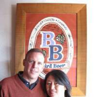 Bryan and Sayuri Baird pose in front of the Baird Beer logo at The Fishmarket Taproom in Numazu, Shizuoka Prefecture. | KRIS KOSAKA PHOTO