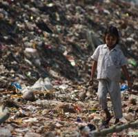 Not sweet: A child refugee walks through the garbage of the Mae Sot dump along the Thai-Myanmar border, where some 70 families make their homes after fleeing Myanmar. Below: Myanmarese women stand in front of a hut on the Mae Sot garbage dump.   COURTESY OF EL-BRANDEN BRAZIL