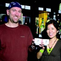 Johnnie Stroud and his wife Taiko raise sake cups at their Sake Nomi shop in Seattle. | COURTESY OF JOHNNIE STROUD