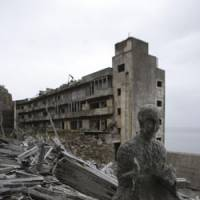 Coal comfort: A Buddhist statue on Hashima Island off Nagasaki — commonly known as Gunkanjima (Warship Island) — which was abandoned after its coal mine closed in 1974. | JUN NAKASUJI PHOTO