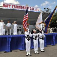 Yokosuka Mayor Yuuto Yoshida is flanked on the stage by Capt. David Owen (left), commander of the U.S. base, and Rear Adm. Shinsuke Miki, chief of staff of the Maritime Self-Defense Force Yokosuka district, as they salute during the event's opening ceremony. | YOSHIAKI MIURA PHOTO