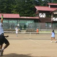 Big shots: Michael Mentzer and Sanae Ota (far court) compete in the final of the mixed doubles competition at the Karuizawa International Tennis Tournament earlier this month (left). | EDAN CORKILL PHOTO