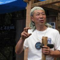 Top man: Event organizer Kunihiro Amemiya with his stone ax.