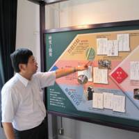 Plan of attack: Museum curator Akira Yamada points to a panel explaining biological warfare research conducted at the Noborito laboratory. | MARK SCHREIBER PHOTO