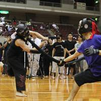 Battle ready: Two children compete in datotsu kyogi (hitting games). Below: Practitioners fight during a game.   JAPAN SPORTS CHANBARA ASSOCIATION
