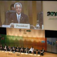In the hot seat: Ryu Matsumoto, Japan's environment minister and president of the COP10 gathering in Nagoya, is projected on screen as he sits surrounded by other officials and delivers his opening address to delegates on Oct. 18. | WINIFRED BIRD PHOTO