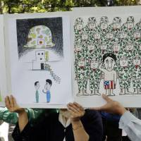 Fair satirical game: Protesters hold posters ridiculing Prime Minister Shinzo Abe during a rally against the Liberal Democratic Party's plan to amend the Constitution on March 3, the Constitution Day national holiday, in Tokyo. | AP
