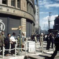 Look at the past: A 1945 photo by by Gaetano Faillace shows the building of Hattori Tokei-ten (K. Hattori & Co. — the predecessor of Seiko Holding Corp.), requisitioned for use as a U.S. military commissary, at the Ginza 4-chome intersection.