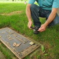 Lest we forget: Rick Miller, cofounder of Digital Legacys, uses a customized smartphone app to read a QR code on a memorial plaque. | AFP-JIJI