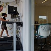 Taking health in their stride: Michelle Schneider and Dave Dunn use treadmill desks at Evolent, a health-care startup in Arlington, Virginia. Researchers are trying to determine whether the equipment allows people to burn off glucose that accumulates in the bloodstream. | THE WASHINGTON POST