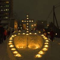 Lit candles cross the Temiya Line in Otaru