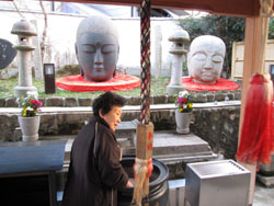 Kimiyo Kitagaki 'tidies' ashes at Kubi Jizo shrine. | SIMON BARTZ
