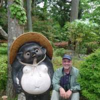 A fine pair: The author (right) sits beside a stately  tanuki  (raccoon dog) statue at secluded Komponji Temple.