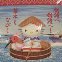 Catamaran: Hello Kitty, clad in Sado dance gear, paddles a Sado round boat aided by Toki, a Sado crested ibis.