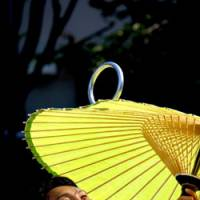 Eye-opener: An  Edo daikagura  (traditional juggler) spins a silver hoop on his parasol in the grounds of ancient Daikyoji Temple.