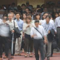 Not much jingling: Morning commuters exit Tokyo Station last week. The average Japanese husband's monthly allowance slumped to the lowest level since 1982. | BLOOMBERG