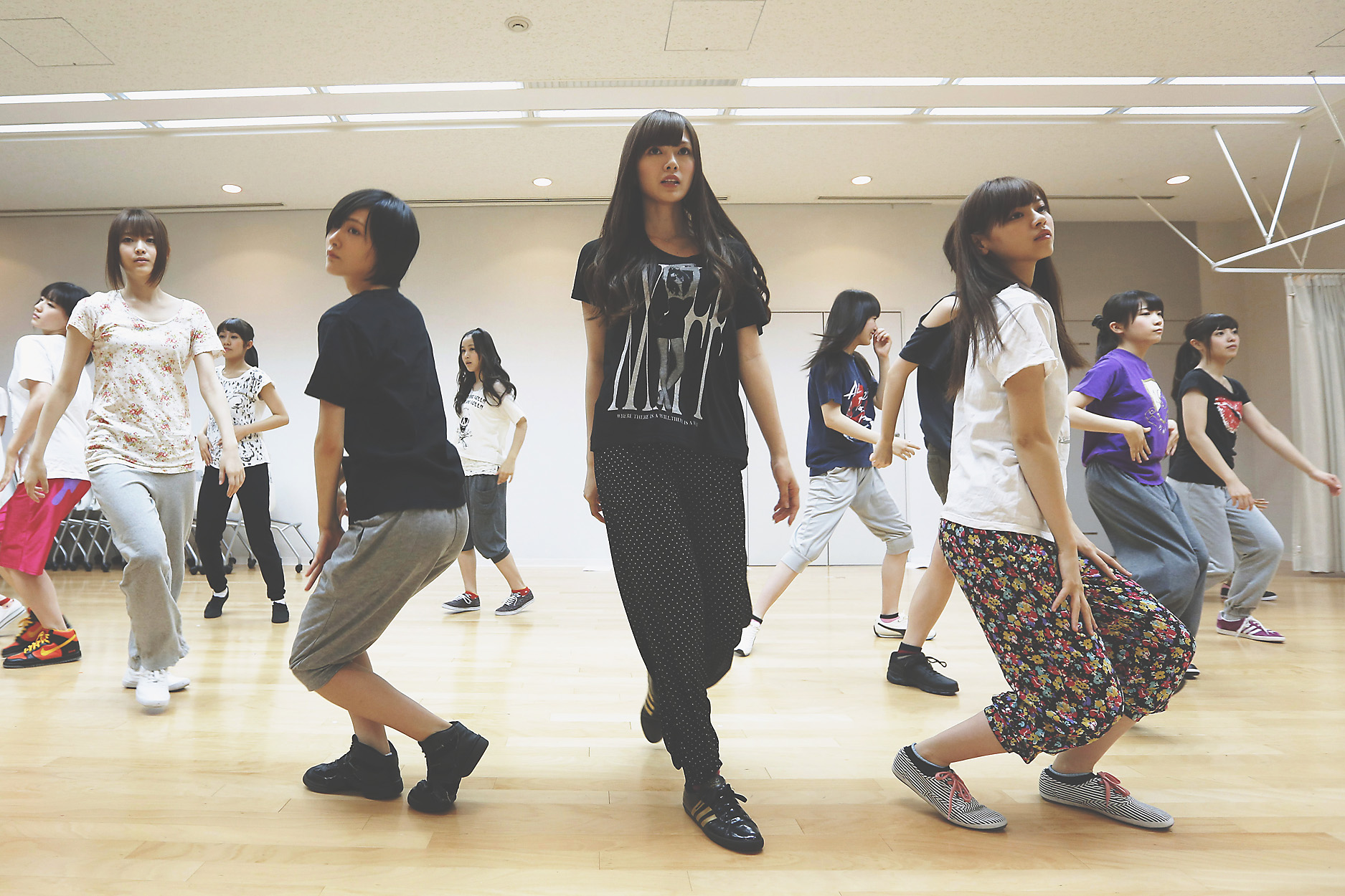 Seeking a toehold: Members of Sony Corp.'s girl group Nogizaka 46, (from front left) Sayuri Matsumura, Rina Ikoma, Mai Shiraishi and Nanase Nishino, practice dance moves for a new song with colleagues at Sony Music Entertainment (Japan) Inc. headquarters in Tokyo on June 28. | BLOOMBERG