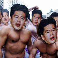 Inspired: Supporters of brash Internet entrepreneur Takafumi Horie, the former president and CEO of Livedoor Co. Ltd., pose in masks representing Horie in front of the Tokyo District Court in March 2007. | BLOOMBERG