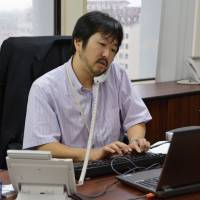 Legal foothold: Lawyer Yusuke Yukawa, a representative of Nishimura & Asahi LPC's office in Yangon, works at the office June 10. Japan's biggest law firm established the office in Myanmar's largest city in May. | KYODO