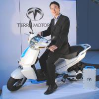 Smart scooter: Toru Tokushige, president of Terra Motors Corp., touches an iPhone mounted on his company's electric A4000i scooter in Koto Ward, Tokyo, on Wednesday. | SATOKO KAWASAKI