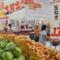 The price is right: Shoppers check out vegetables offered at discount prices at an Ito-Yokado supermarket in Katsushika Ward, Tokyo, on Wednesday. | KYODO