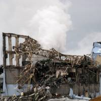 Four-decade 'accident': The remains of the No. 3 reactor building smolder at the Fukushima No. 1 power plant in the town of Okuma, Fukushima Prefecture, on March 15, 2011, after a hydrogen explosion blew it apart. | TOKYO ELECTRIC POWER CO./AFP-JIJI