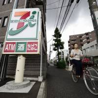 A matter of convenience: A woman bicycles past a 7-Eleven convenience store in Kawasaki on May 28. | BLOOMBERG