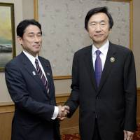 One more try: Foreign Minister Fumio Kishida (left) and South Korean counterpart Yun Byung-se exchange greetings ahead of bilateral talks Monday in Bandar Seri Begawan in Brunei held on the sidelines of the ASEAN conference. | KYODO