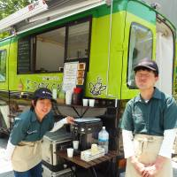 Shinobu Honda (left) and Naoya Ogane, staff at Shibuya Park Cafe, a mobile catering wagon, sell sandwiches and coffee in Miyashita Park in Shibuya Ward in May. | KYODO