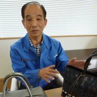 Socially conscious: Akio Sato, who launched a factory to make leather bags in Minamisanriku, Miyagi Prefecture, shows off some of his products April 22. | KYODO