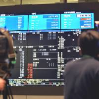 Going public: TV crews film a board flashing the numbers of Suntory Beverage & Food's listing Wednesday on the Tokyo Stock Exchange. | AFP-JIJI