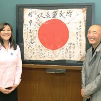 Rightful place: Tadataka Hoshi (right) and Aki Suzuki, a teacher at a U.S. university, pose for a photo Saturday in front of a Hinomaru flag that belonged to Hoshi's father and was returned to him via Suzuki at Senju police station in Tokyo. | KYODO