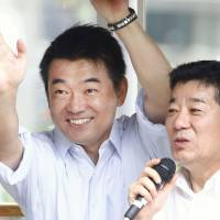 Glad-handing: Nippon Ishin no Kai co-leader Toru Hashimoto (left) and Secretary-General Ichiro Matsui wave to voters in Osaka at the start of Upper House election campaigning Thursday.   KYODO
