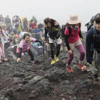 Because it's here: Hikers reach the seventh station of one of Mount Fuji's climbing trails on June 30, the day before the famed volcano's climbing season officially opened. | KYODO