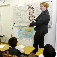 Building blocks: An instructor teaches young children in English, using a DNA model, at S&S International School in Yokohama on May 29. | KYODO