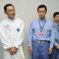 Damage control: Masao Yoshida (left), the late former chief of the Fukushima No. 1 nuclear plant, speaks to reporters at the plant in November 2011 as Goshi Hosono, then Cabinet minister in charge of the crisis, looks on. | KYODO
