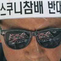 Anti-glare: Rising Sun flags are reflected in a protester's sunglasses during an anti-Japan demonstration in front of the residence of the Japanese ambassador in Seoul on May 21. | AP