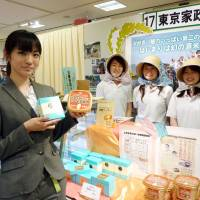 High-tech produce: Students from Tokyo Kasei University, which has produced sweets safe for children allergic to wheat, eggs and dairy products, and Nari Takahashi (front), a graduate of the university, pose for a photo on June 4 at a promotional fair at Takashimaya's Shinjuku store in Tokyo's Shibuya Ward. | KYODO