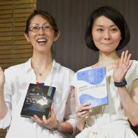 Laureates: Naoki prize winner Shino Sakuragi (left) and Akutagawa award winner Kaori Fujino hold their award-winning books Wednesday at a press conference in Tokyo. | KYODO