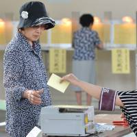 One ballot at a time: A woman receives her ballot for the Upper House election from an election board official at a polling station in Tokyo on Sunday. | AFP-JIJI