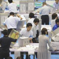 Long night ahead: Election staff count ballots Sunday evening in Minato Ward, Tokyo, after the polls closed. | KYODO