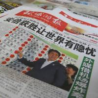 Above the fold: The Liberal Democratic Party's landslide victory in the Upper House election is featured in a newspaper at a Shanghai newsstand on Monday. | AP