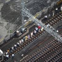 Single-file please: Passengers from a stranded train on the Tokyu Toyoko Line in Kawasaki are forced to get out and walk toward Motosumiyoshi Station after a thunderstorm caused a power outage Tuesday afternoon. | KYODO