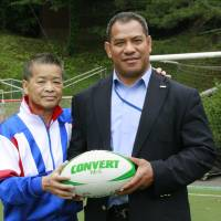 On the field: Sinali Latu (right) a retired rugby player for the Japan national team from Tonga, and Yasuyuki Kagami, a former coach of the Daito Bunka University rugby club, pose for a photo at the university's rugby field in Higashimatsuyama, Saitama Prefecture, in May. | KYODO