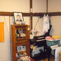In remembrance: Photos of the late Yoshitaro Azuma are seen at an altar in the home of his wife, Yoshino Azuma, in Tokyo's Sumida Ward on July 12. The 43-year-old widow was denied welfare benefits despite working two part-time jobs and raising four kids on her own. | TOMOHIRO OSAKI