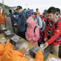 Peak toll: Visitors pay a voluntary ¥1,000 admission fee to climb Mount Fuji as Yamanashi and Shizuoka prefectures introduced the charge on a trial basis Thursday morning. | KYODO